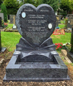 Polished Bahama Blue granite Edingly heart headstone with hand carved rose. Granite Grave kerb set installed on matching all polished granite plinth fitted in front of headstone.