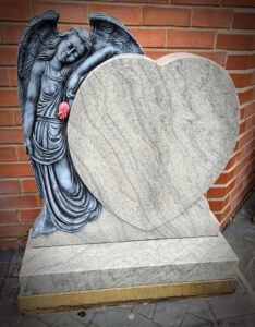 Carved Angel holding a red rose resting on heart shaped gravestone